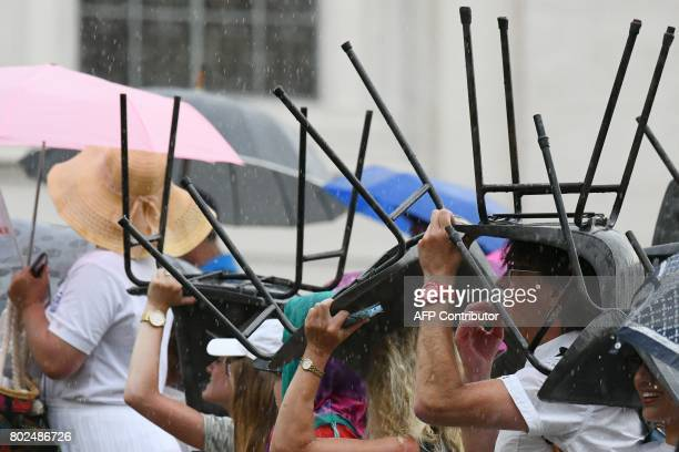 People protect themselves from the rain with chairs during Pope Francis' weekly general audience at St Peter's square on June 28 2017 in Vatican /...