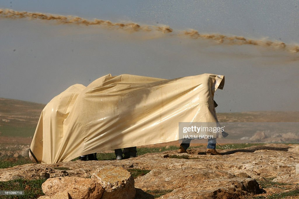 People protect themselves under a tent as Israli soldiers spray foul-smelling water to disperse Palestinian activists trying to set up a new encampment to protest against settlement building in the Yatta, south of the West Bank city of Hebron on February 9, 2013. Soldiers dismantled tents that were being erected in two different areas near the town of Yatta, and forced activists to leave, the Palestinian witnesses said. BADER