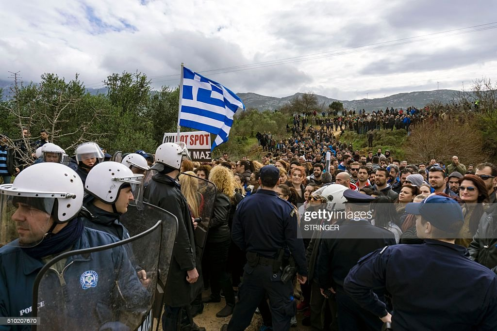People protest against the so-called 'hotspot' being built for refugees and migrants on the Aegean island of Kos, on February 14, 2015. Greek riot police fired tear gas at demonstrators protesting against the development of a centre to house migrants on the tourist island of Kos, media reports said. About 2,000 people joined a rally against the so-called 'hotspot' being built on the Aegean island despite the opposition of local residents and the mayor, fearful of the effect on the vital tourism industry. / AFP / Eurokinissi / STRINGER