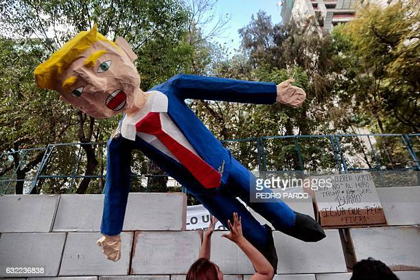 People protest against US President Donald Trump's inauguration next to a fake wall with a dummy representing him in Mexico City on January 20 2017...