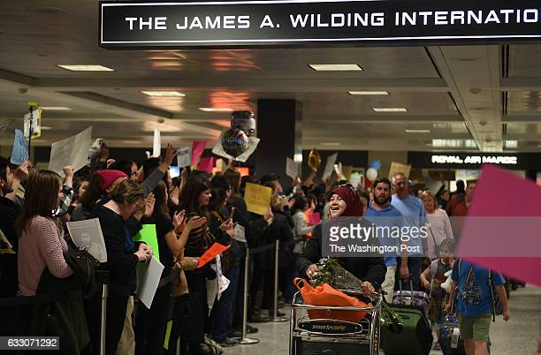 People protest and welcome arriving passengers at Washington Dulles International Airport in Virginia January 28 2017 The protest follows the...
