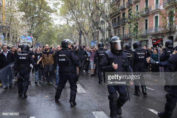People protest as police try to control the area in their attempt to cast their ballot today at a polling station in the referendum vote on October 1...