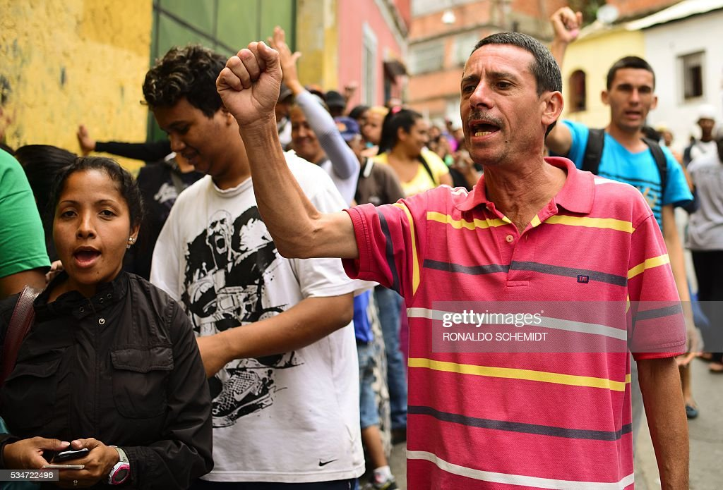 People protest as they line up to buy basic food and household items outside a supermarket in the poor neighborhood of Lidice, in Caracas, Venezuela on May 27, 2016. / AFP / RONALDO