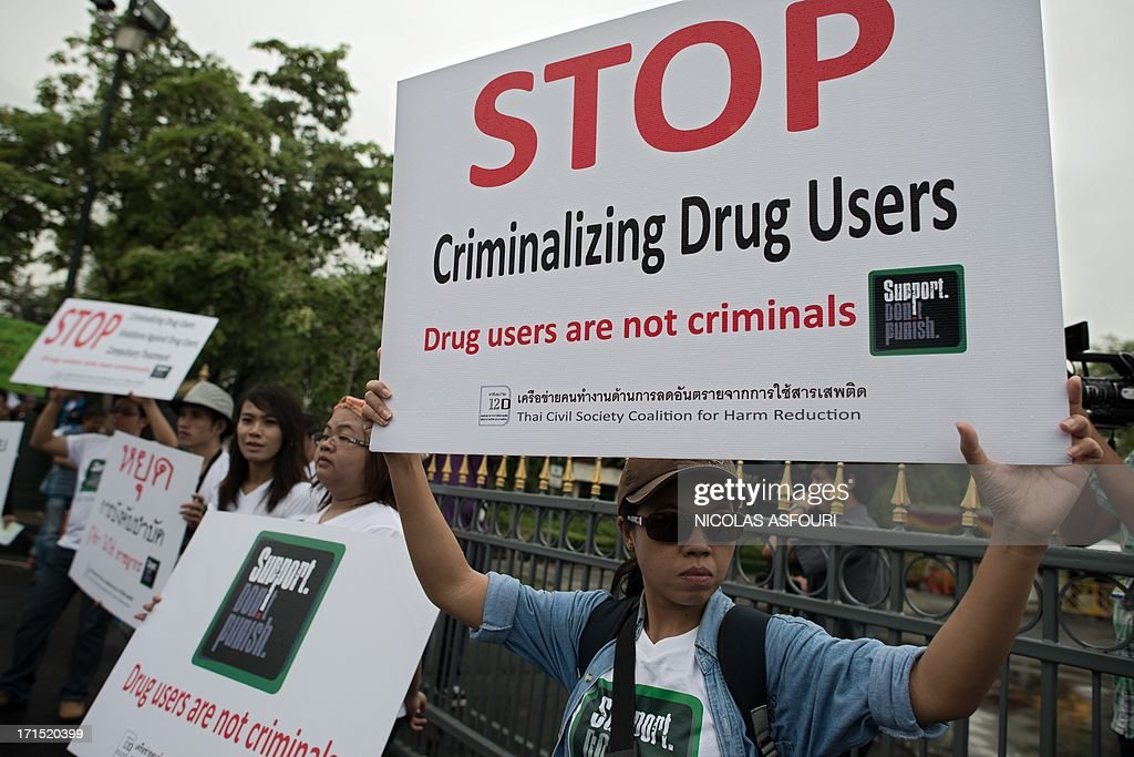 People protest with banners saying 'drug users are not criminals' and 'Stop criminalizing drug users' in front of Government house in Bangkok on June 26, 2013. The protest was staged on the international day against drugs. AFP PHOTO/ Nicolas ASFOURI