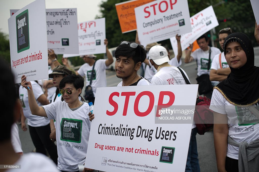 People protest with banners saying 'Stop criminalizing drug users' in front of Government house in Bangkok on June 26, 2013. The protest was staged on the international day against drugs. AFP PHOTO/ Nicolas ASFOURI