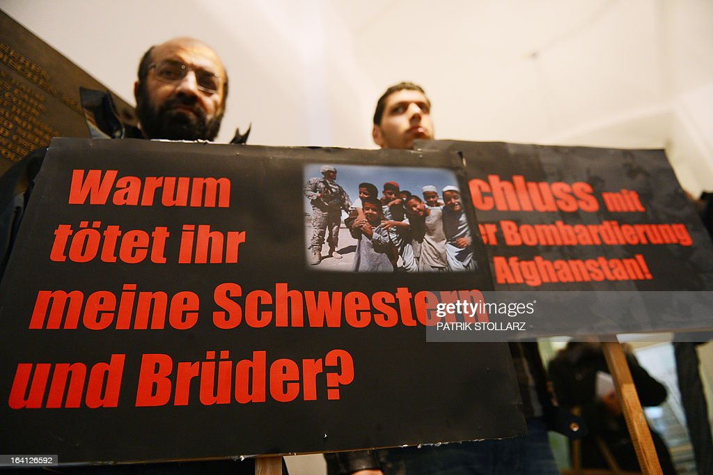 People protest with placards reading 'Why did you kill my sister and brother ?' at the Regional Court in Bonn, western Germany on March 20, 2013 prior to the trial for 91 victims who died in Kundus in September 2009 after US bombers destroyed two gas trucks ordered by a German colonel Georg Klein.