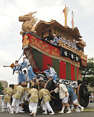 People pull a huge decorated float as they turn it around a corner on a street in Kyoto on July 24 during the 'Ato Matsuri' or latter half of the...