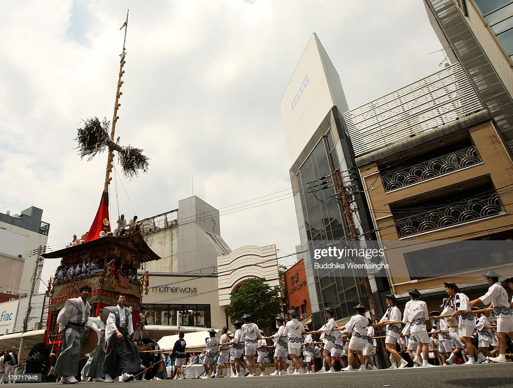 People pull float named Yamahoko during the annual Kyoto Gion Festival on July 17, 2013 in Kyoto, Japan. The Gion festival is one of three biggest Japanese festivals. dating back to the 9th century, the festival is part of a ritual intended to satisfy the Gods that brought on fire, floods and earthquakes. During the festival the streets are decorated with lanterns and many of the women dress in 'yukata', summer kimonos.