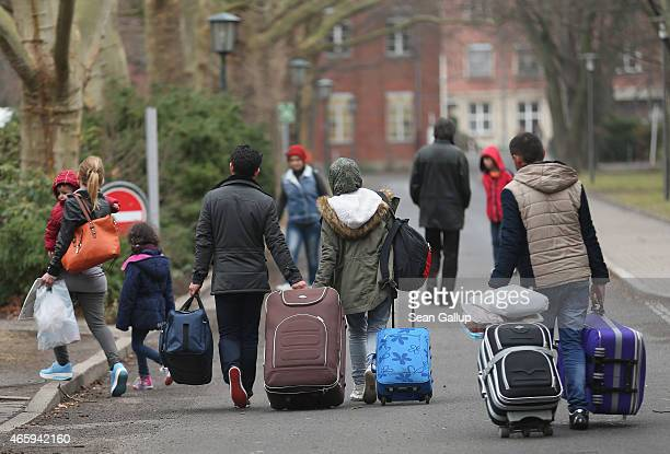 People pulling suitcases arrive at the Central Registration Office for Asylum Seekers of the State Office for Health and Social Services which is the...