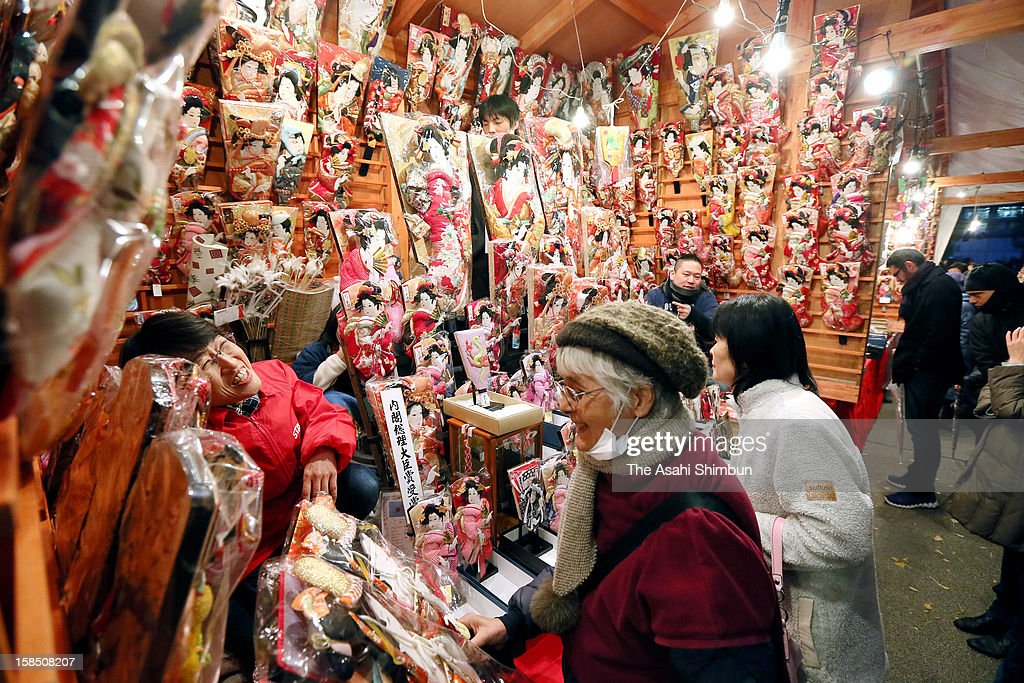 People purchase decorated Hagoita wooden puddles at Hagoita market at Sensoji Temple on Deecember 17, 2012 in Tokyo, Japan. 50 stalls are arranged during the annual event, which opens till December 19.