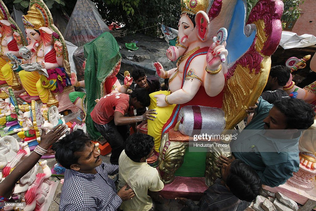 People purchase idols of Lord Ganesha ahead of Ganesha Chaturthi, in Mayur Vihar area on September 8, 2013 in New Delhi, India. Ganesh Chaturthi, which begins from September 9, is celebrated as the birthday of Lord Ganesha who is widely worshiped by Hindus as the god of wisdom, prosperity and good fortune.