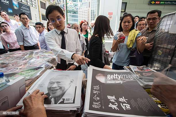 People purchase special edition newspapers following the death of Singapore's first elected Prime Minister Lee Kuan Yew at Raffles Place in Singapore...