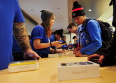 People purchase the Apple iPhone 5 at the Apple Store on Fifth Avenue September 20 2013 in New York Some people waited as long as fifteen days in...