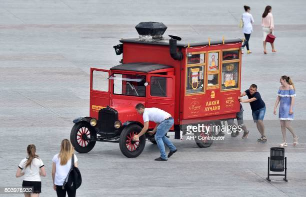 People push a brokendown vehicle in downtown Kiev on June 30 2017 amid an ongoing heatwave Half a degree Celsius of global warming has been enough to...