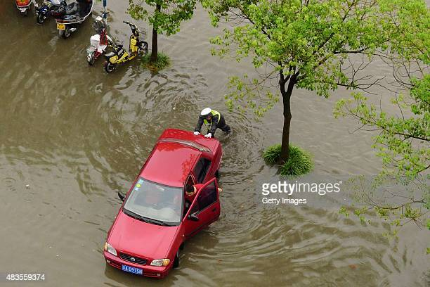 People push a car in flood waters caused by a major rainstorm on August 10 2015 in Yangzhou Jiangsu Province of China Typhoon 'Soudelor' has brought...