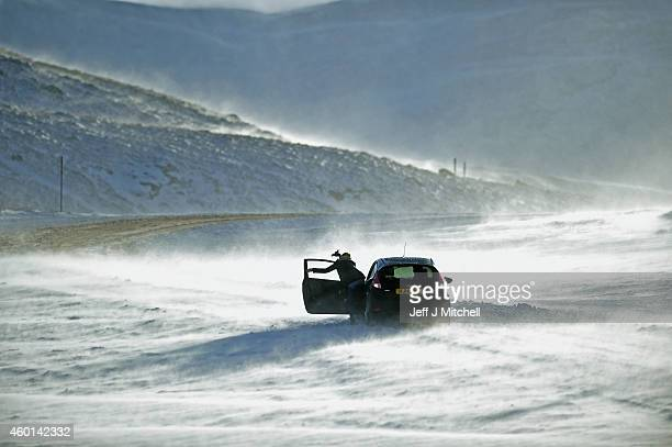 People push a car stuck on the A93 Braemar to Glenshee road as snow is forecast for much of the UK on December 8 2014 in Glenshee Scotland The Met...