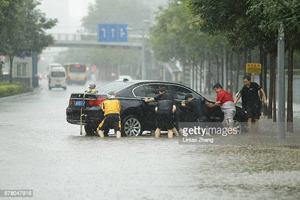 People push a car through a flooded street on July 20 2016 in Beijing China Heavy rainfall hit capital Beijing and Beijing Meteorological...