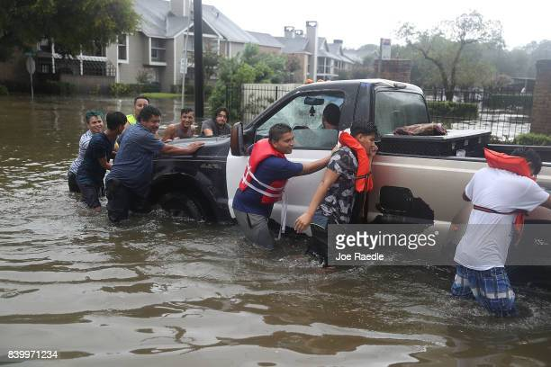 People push a truck down a flooded street after the area was inundated with flooding from Hurricane Harvey on August 27 2017 in Houston Texas Harvey...