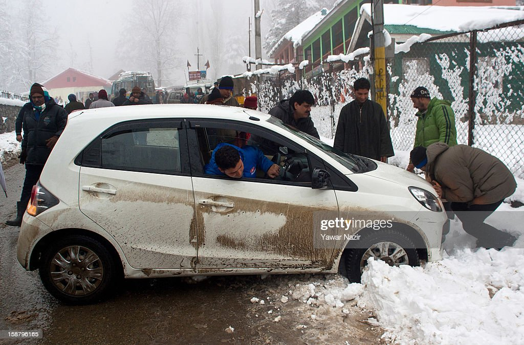 People push a vehicle that lost control on the road during a snowfall on December 29, 2012 in Gulmarg, 54 km (35 miles) to the west of Srinagar, the summer capital of Indian-administered Kashmir, India. With the second round of heavy snowfall in Kashmir valley, skiers from around the globe have descended on the ski resort of Gulmarg, known for long-run skiing, snow-boarding, heli-skiing and steep mountains. Gulmarg is located less than six miles from the ceasefire line or Line of Control (LoC) that divides Kashmir between India and Pakistan. As a sense of normalcy has started to return to this strife-torn region, various foreign governments, including the United Kingdom, have lifted the travel advisory to its citizens traveling to Kashmir, raising the hopes of the local tourism industry, officials said.