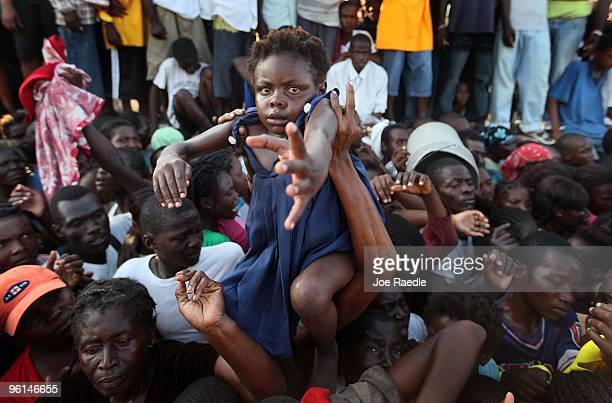 People push forward to receive food being given out by the Yele Haiti foundation for those displaced by the massive earthquake on January 24 2010 in...