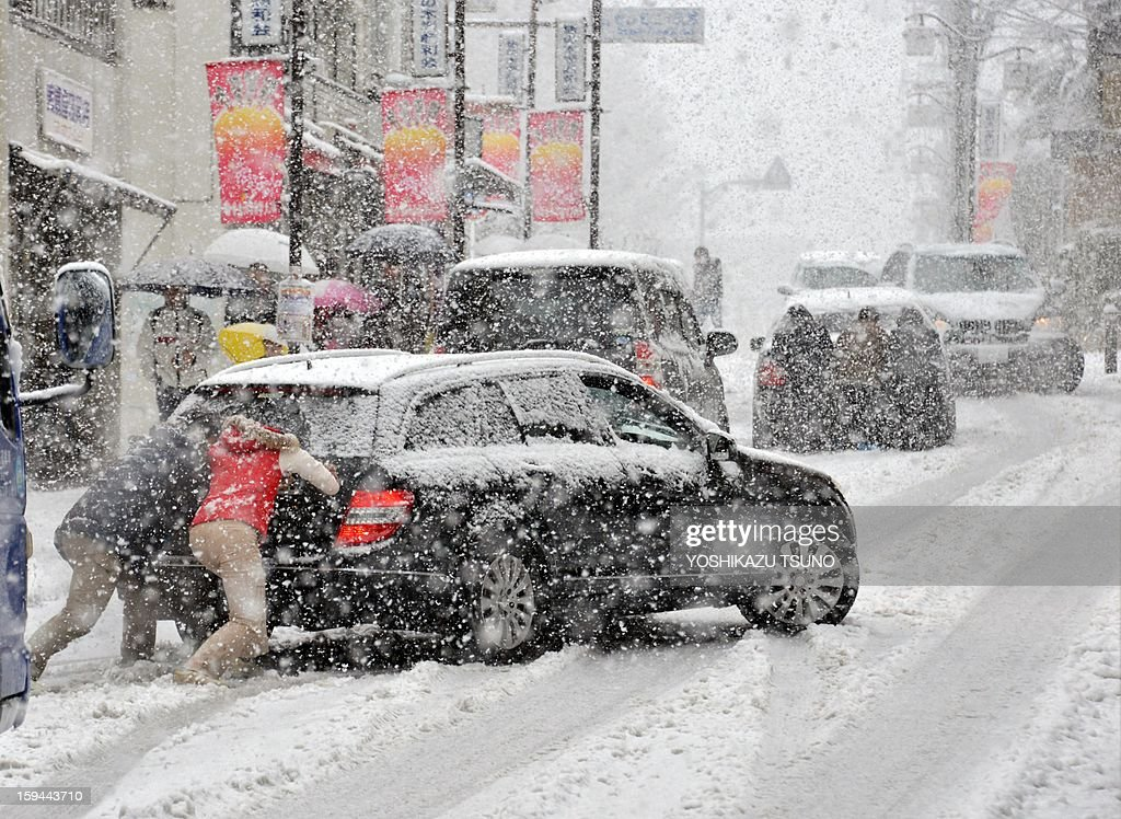 People push vehicles after they lost traction and skidded on a snow and ice covered road in Tokyo on January 14, 2013. A storm system grasped central Japan on January 14, causing heavy snow fall around the Japanese capital. AFP PHOTO / Yoshikazu TSUNO