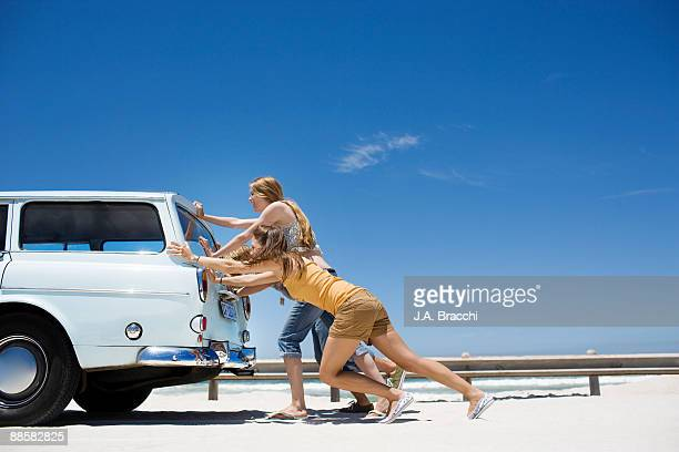 People pushing broken down car at beach
