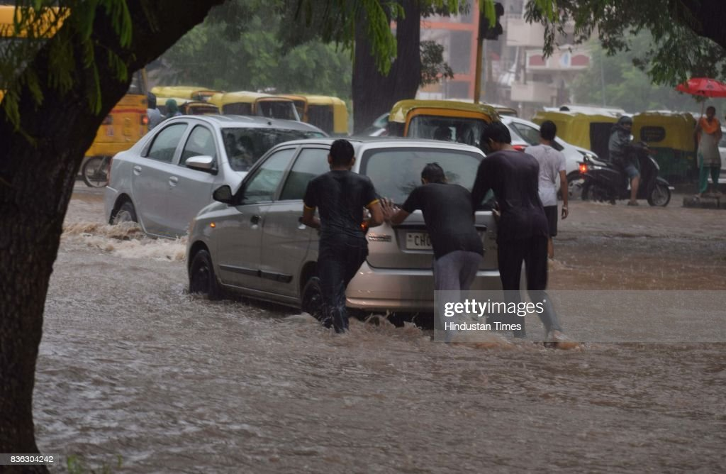 People pushing car as it broke down due to water-logging after heavy rains at sector 41 on August 21 2017 in Chandigarh, India. Heavy rainfall on morning brought the tri-city (Chandigarh, Mohali, Panchkula) to a stand still as poor drainage system gave way to roads being flooded with water. The rainfall left the cars of commuters stuck in middle of the roads forcing them to leave their cars stranded.