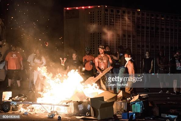 People put cargo from tractor trailers on a fire on the I85 during protests in the early hours of September 21 2016 in Charlotte North Carolina The...