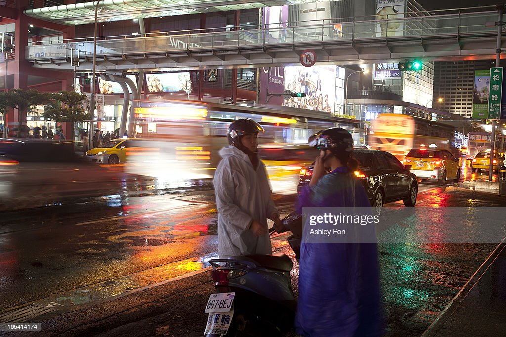 People put on a rain jacket to avoid a downpour at night in the shopping district in Taipei's Hsin-yi district on April 3, 2013 in Taipei, Taiwan. Franchise and chain operations in Taiwan's retail and food sectors make up 50 per cent of sales, and 25 per cent of the service sector.