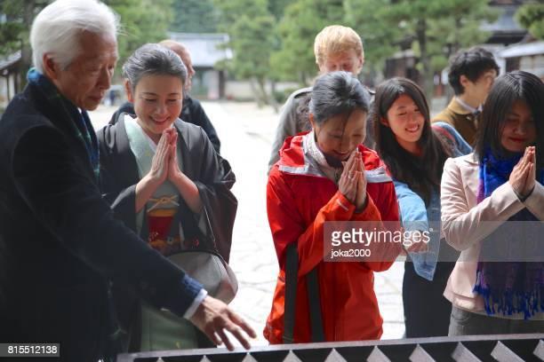 人々 の寺院の前に彼らの手を一緒に入れて