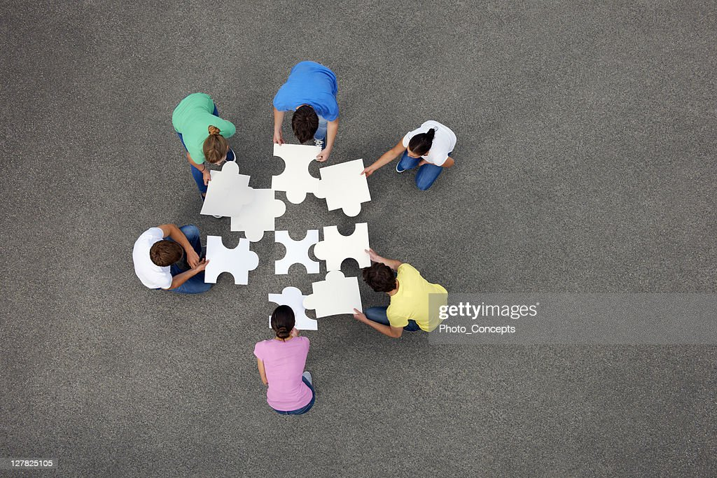 People putting together jigsaw puzzle : Stock Photo