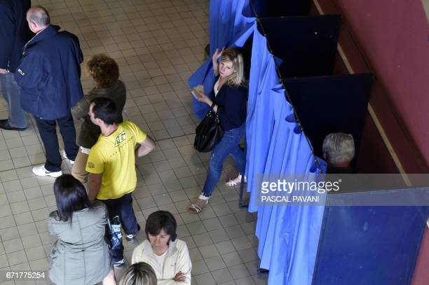 People queue at a polling station in MartresTolosane southwestern France on April 23 during the first round of the Presidential elections / AFP PHOTO...