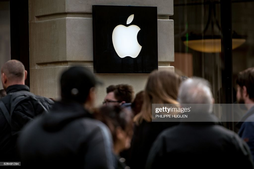 People queue at an Apple store in Lille on April 30, 2016. / AFP / PHILIPPE
