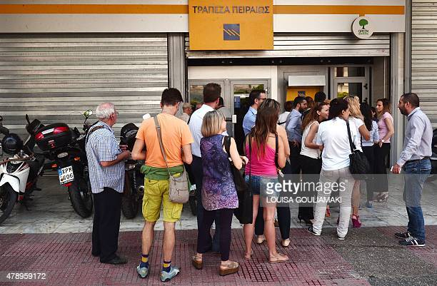 People queue at the ATM machines of the Piraeus bank in central Athens after the opening of the transactions on June 29 2015 Greece ordered its banks...