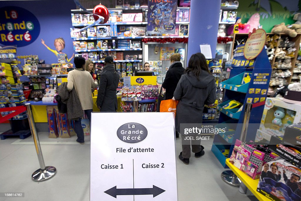 People queue at the cash desk of a toy store, on December 21, 2012 at the Kremlin-Bicetre, outside Paris.