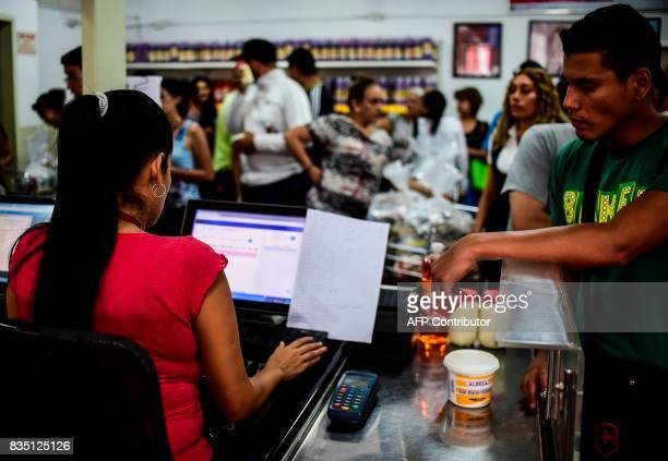 People queue at the checkout counter at one of the food distribution centers called CLAP which are run by community leaders in a neighbourhood of...