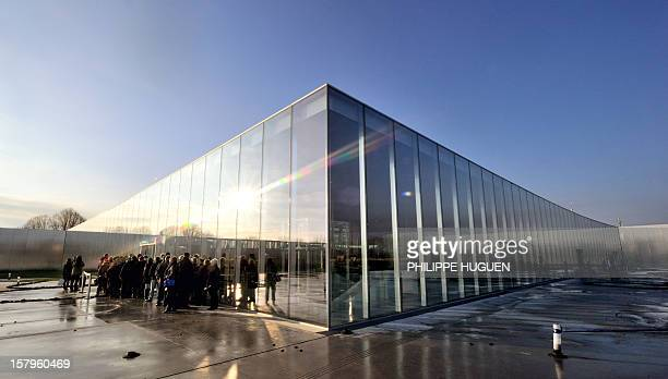 People queue at the entrance of the LouvreLens museum on December 8 2012 in Lens northern France The Louvre museum opened a new satellite branch...
