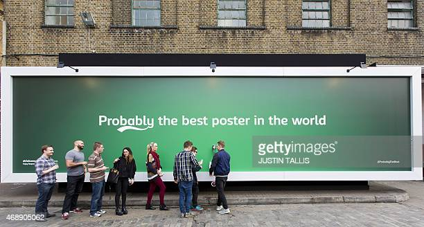 People queue by a billboard poster with a built in tap that is dispending free beer outside the Truman Brewery in east London on April 8 2015 The 12...