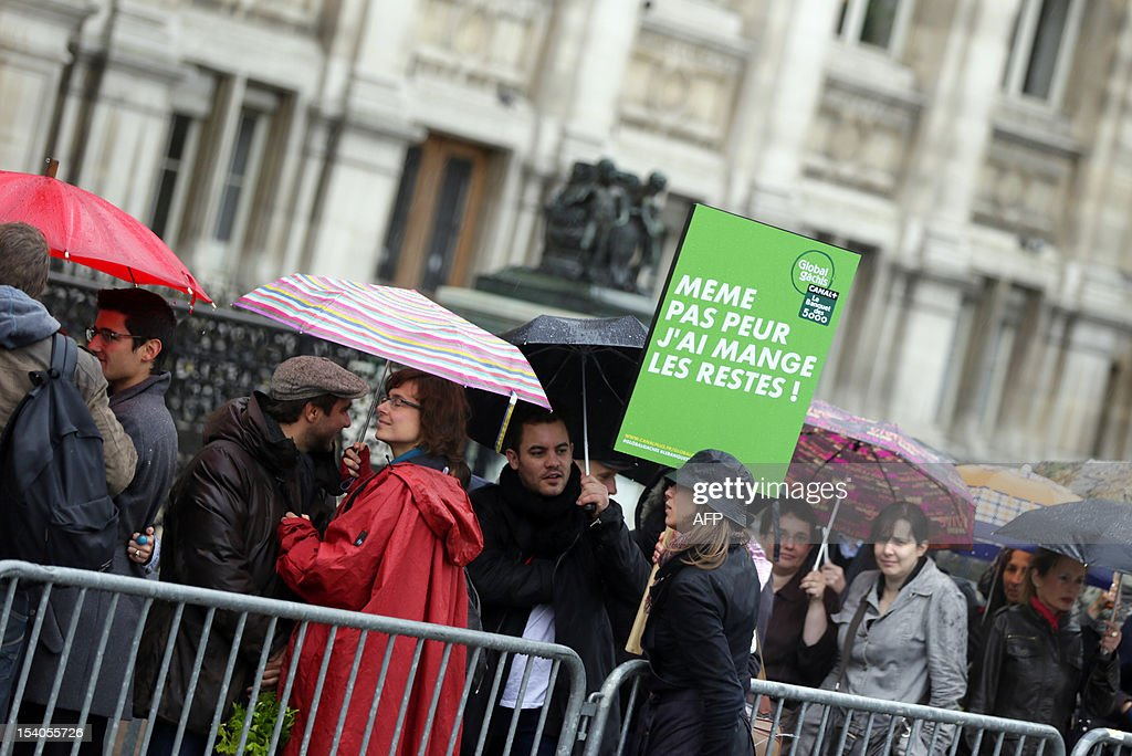 People queue during an event to raise awareness of the food waste on October 13, 2012 at the Place de l'Hotel de Ville in Paris. Five thousand people were invited to enjoy a giant curry prepared using 800 kg of twisted carrots and uncalibrated vegetables that supermarkets refuse to buy from producers and which usually end in disposal. 'While one billion people suffer from malnutrition in the world, a third of the food produced ends up in the trash! I am green since I was 4 years' said Tristram Stuart, British author and activist.
