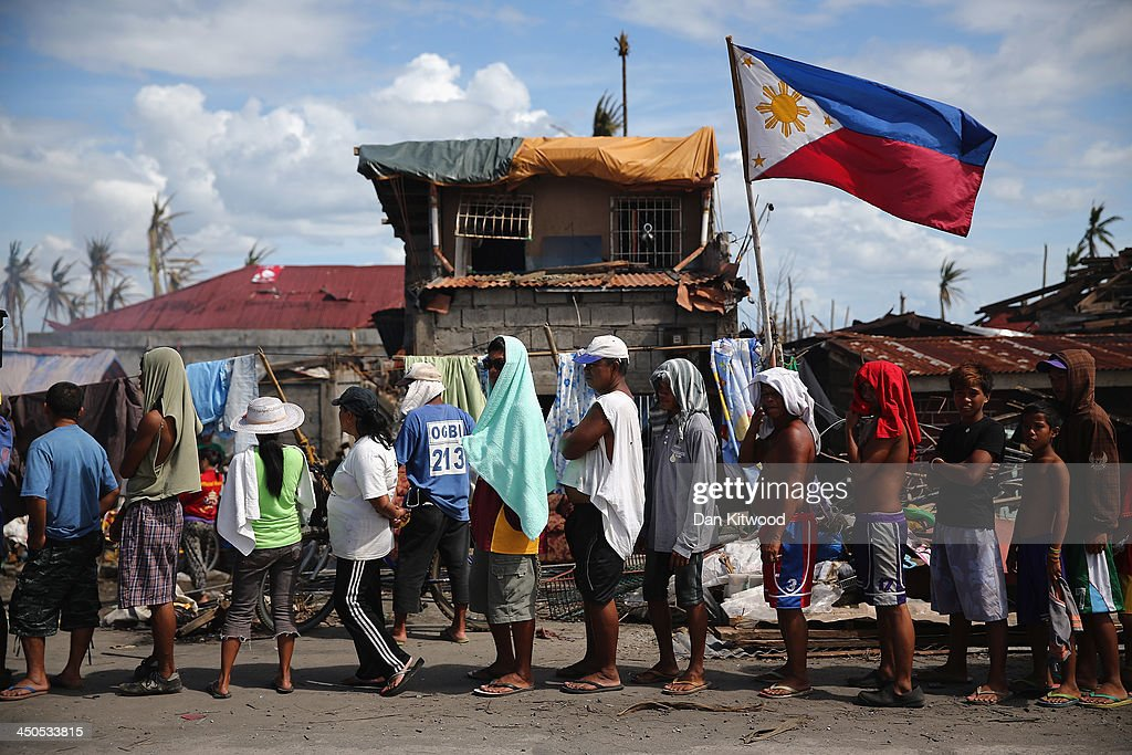 People queue for aid in Tananau on November 19, 2013 in Tananau , Leyte, Philippines. Typhoon Haiyan which ripped through Philippines over a week ago has been described as one of the most powerful typhoons ever to hit land, leaving thousands dead and hundreds of thousands homeless. Countries all over the world have pledged relief aid to help support those affected by the typhoon however damage to the airport and roads have made moving the aid into the most affected areas very difficult. With dead bodies left out in the open air and very limited food, water and shelter, health concerns are growing.
