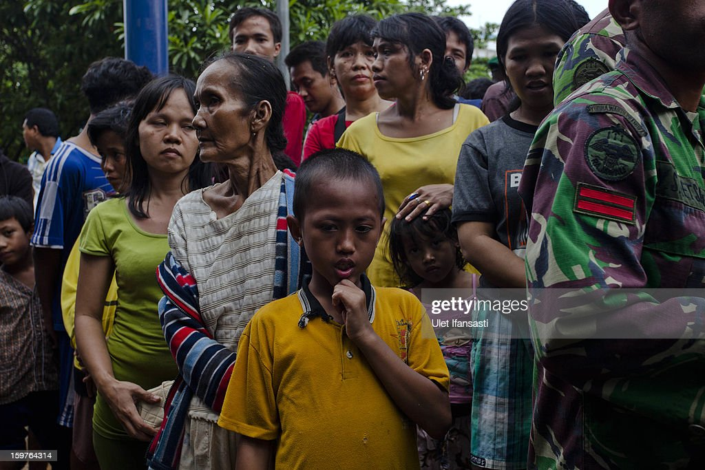 People queue for food aid as major floods hit North Jakarta on January 20, 2013 in Jakarta, Indonesia. The death toll has risen to at least 21 since severe flooding struck the city on January 17. The US has offrered US$150,000 (Rp 1.44 billion) in aid.