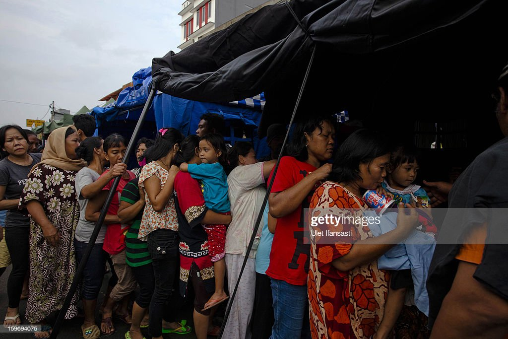 People queue for food and clothing at a temporary shelter in East Jakarta district on January 18, 2013 in Jakarta, Indonesia. According to the National Disaster Management Agency, about 50 percent of the capital is under water following the floods which have so far claimed eleven lives and displaced thousands of Indonesians.