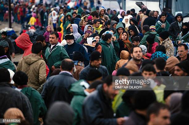 People queue for food at a makeshift camp at the GreekMacedonian border near the Greek village of Idomeni where thousands of refugees and migrants...
