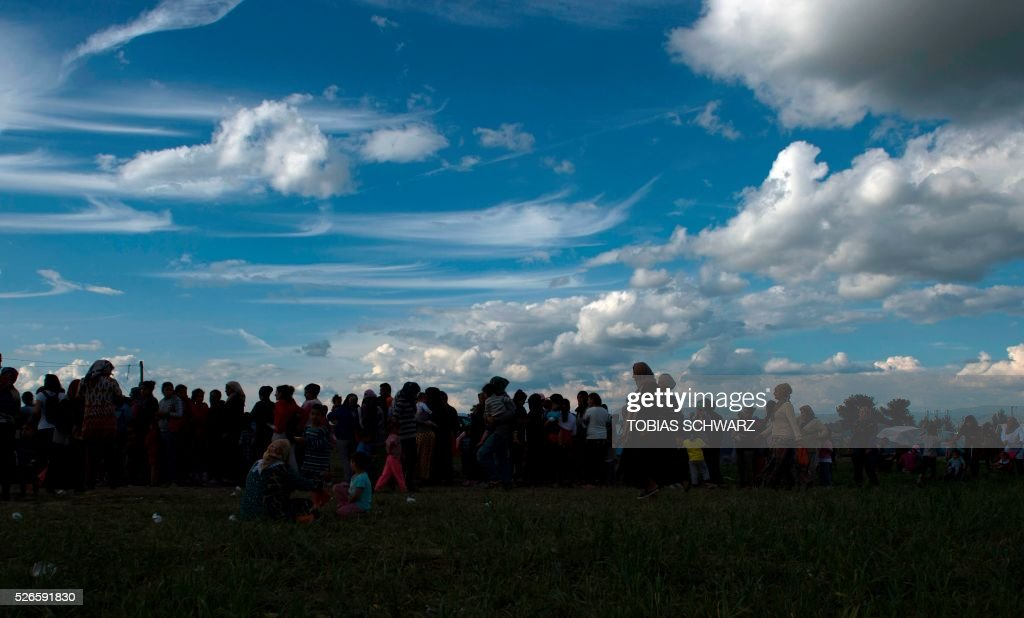 People queue for food at a makeshift camp for migrants and refugees near the village of Idomeni not far from the Greek-Macedonian border on April 30, 2016. Some 54,000 people, many of them fleeing the war in Syria, have been stranded on Greek territory since the closure of the migrant route through the Balkans in February. / AFP / TOBIAS