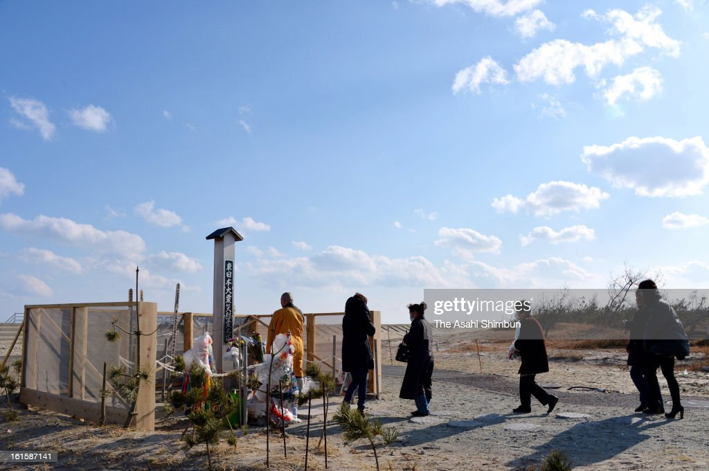 People queue for offering flower bunches at a memorial built at Arahama area, where was washed away by the tsunami on February 11, 2013 in Sendai, Miyagi, Japan. 2 year anniversary approaches though the restoration from the earthquake and tsunami have been delayed.