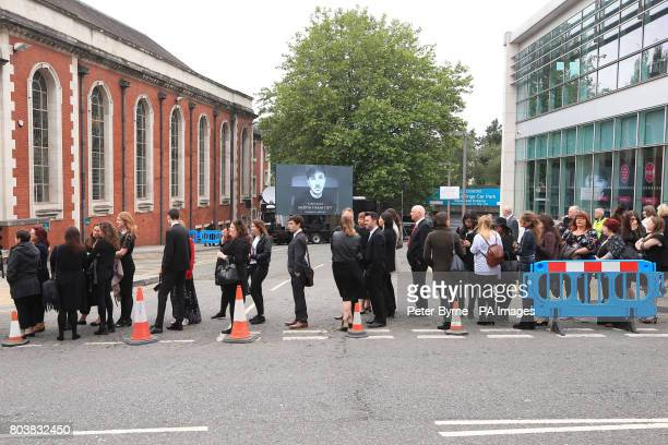 People queue for the funeral service of Martyn Hett who was killed in the Manchester Arena bombing at Stockport Town Hall Plaza