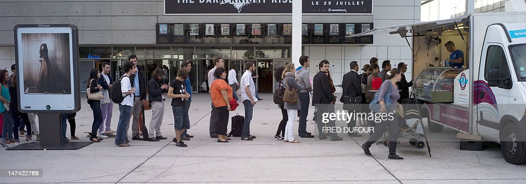 People queue in front of a food truck to buy a hamburger on June 29, 2012 near the National Library in Paris. In the latest American food craze to catch on in France, Parisians are flocking to US-style food trucks for gourmet burgers, artisanal tacos and other decidedly non-French street foods.