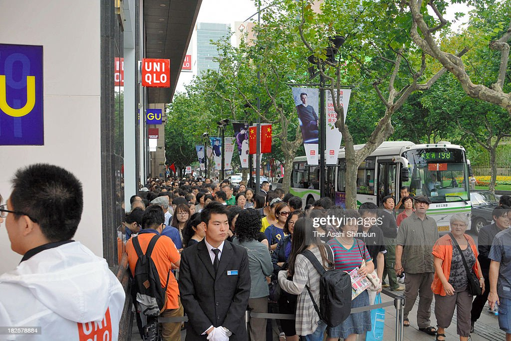 People queue in front of the Uniqlo flagship store opening on September 30, 2013 in Shanghai, China. Casual clothing chain Uniqlo opened its largest outlet yet, a store with 6,600 square meters of floor space in central Shanghai.