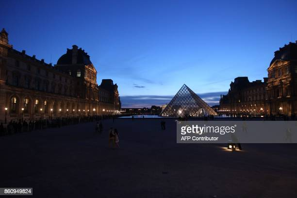People queue next to the entrance of the glass pyramid in the courtyard of the famous Louvre museum to attend the 7th edition of the Museums European...