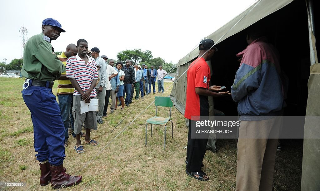 People queue oustside a tent in Chitungwiza to vote at a polling station in a school in Chitungwiza, on March 16, 2013, as voting kicked off for Zimbabwean referendum for a new constitution designed to underpin democratic reforms. AFP PHOTO / ALEXANDER JOE